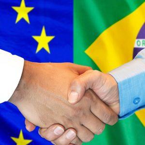 Hand Shake vor Flaggen Brasiliens und der EU