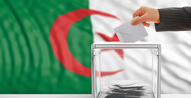 Wahlurne vor Flagge Algeriens