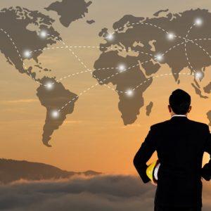Geschäftsmann mit Helm vor Weltkarte